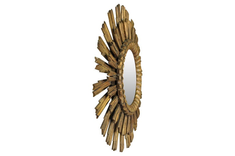 A wonderful early 20th century two-tiered sunburst mirror from Spain. Beautifully carved from giltwood. A wonderful accent piece.