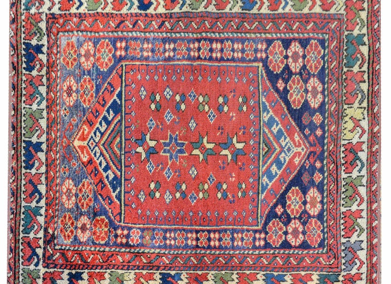 A sweet early 20th century Turkish Sparta rug with a wonderful tribal pattern containing stylized flowers woven in indigo, green, and gold, on a crimson background, on another background with more flowers, and all surrounded by multiple borders