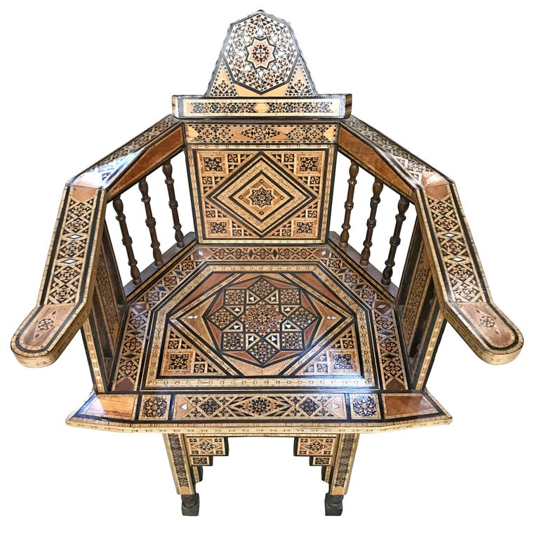 An exciting early 20th century Syrian armchair with elaborately pattern of repeated large and small eight-point stars executed in inlaid exotic and ebonized woods and mother-of-pearl. The sloping arms are supported by turned spindles, and the legs