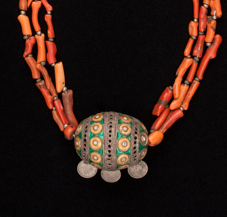 Early 20th century tribal coral pendant necklace, Anti Atlas Mountains, Morocco.  A three-strand antique coral necklace and enameled silver pendant with three hanging silver coins. It measures 28