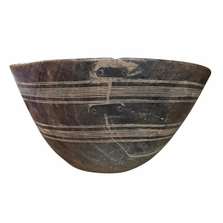 An early 20th century Tuareg bowl carved of a single piece of wood with an incised line pattern around the perimeter, with three beautifully executed repair straps. The Tuareg are nomadic pastoralists who inhabit the Saharan region of Northern