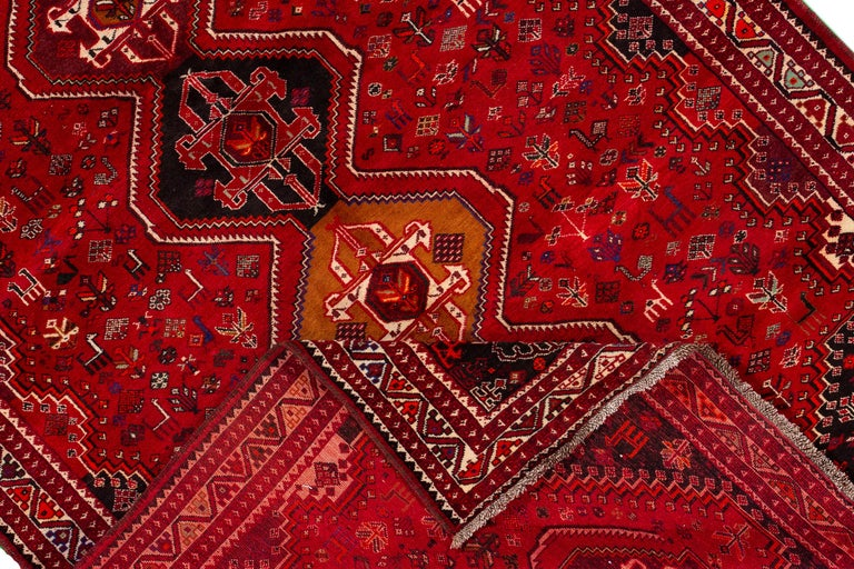 Beautiful vintage Shiraz rug, hand knotted wool with a red field, black and ivory accents, in a center multi medallion design. This rug measures 7' 5