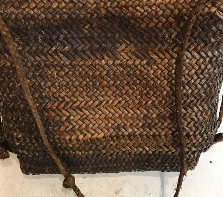 Early 20thcentury woven Thai basket  Beautiful patina    Dimensions: Top is 10.5 in H x 14 in W  Bottom is 10 in H x 13.5 W  Total for basket is 12.5 in H x 14 in W x 4.5 in D with handle 28 in H.