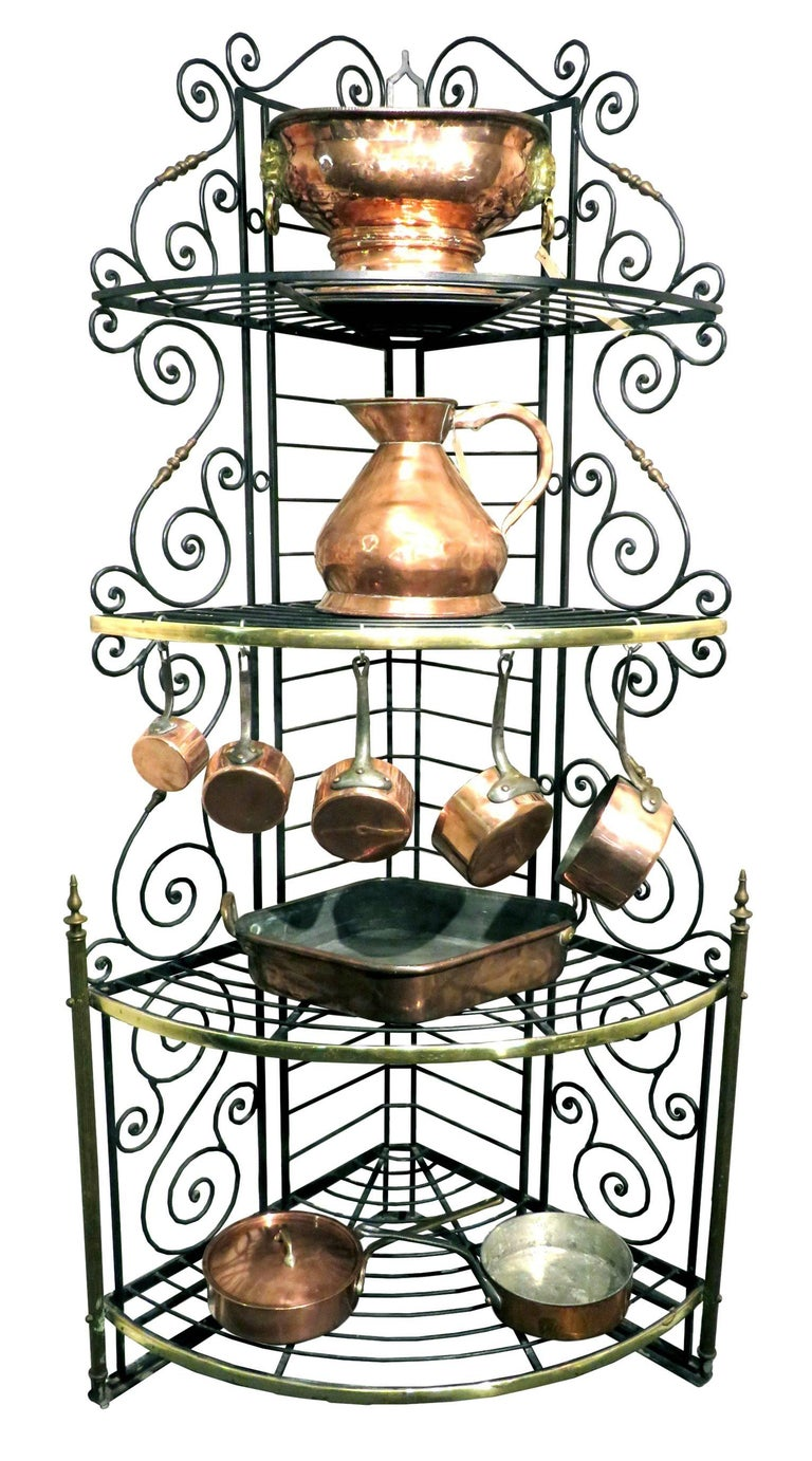 The rugged wrought iron frame fitted with four tiers of graduated demilune shelves - three with conforming brass mouldings, all sided by scrolling 'S' shaped supports interspersed by gilded elements. Corner backer's racks occupy considerably less