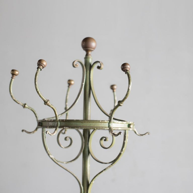 Wrought iron hat and coat stand with brass finals made in France in early 20th century. The decorative design of wrought iron is very nice. One hook is missing.