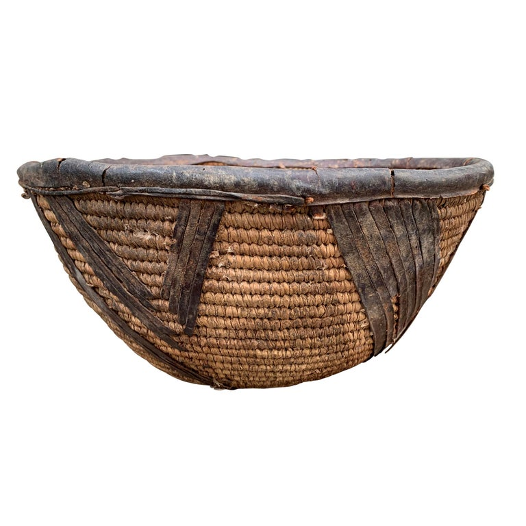 A simple, but chic, early 20th century woven natural fiber basket from the Yoruba People of Nigeria, with leather rim and decorative leather embellishments around the exterior.