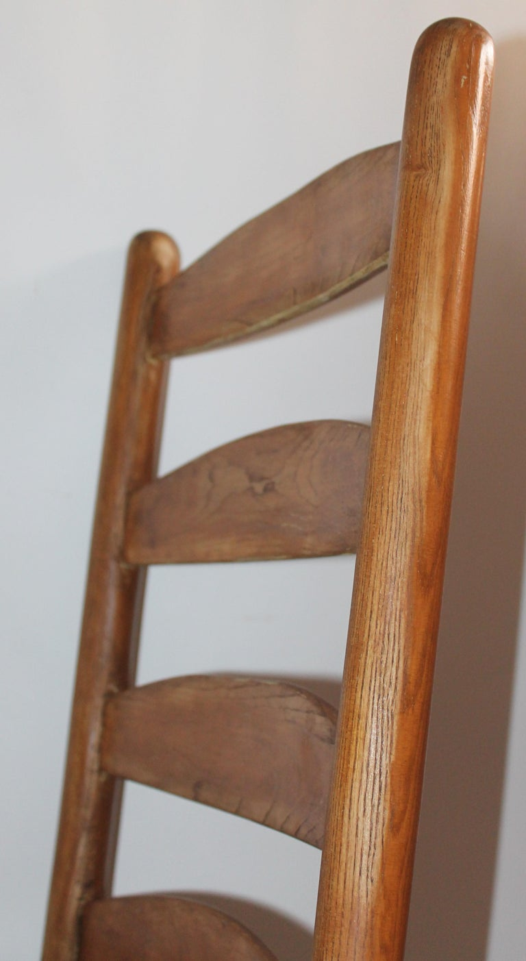This fun and folky mid western ladder back rocking chair is in fine, worn good condition. The original worn patina on the smooth pine wood is fantastic and the sturdy cowhide seat is original to the chair.