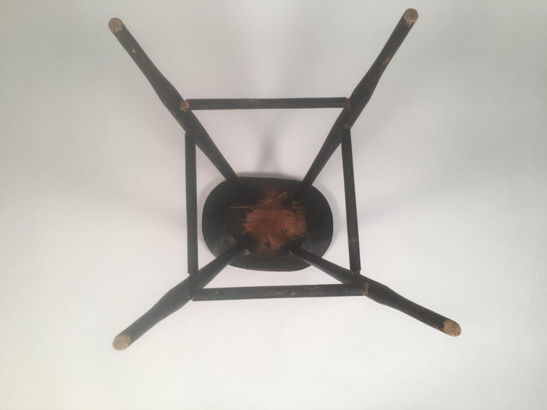 An early American country black painted windsor stool, also the perfect height for a side table, with oval seat, splayed turned and swelled legs, joined by cross stretchers, American, circa 1830.  Incised museum or collector's inventory number on