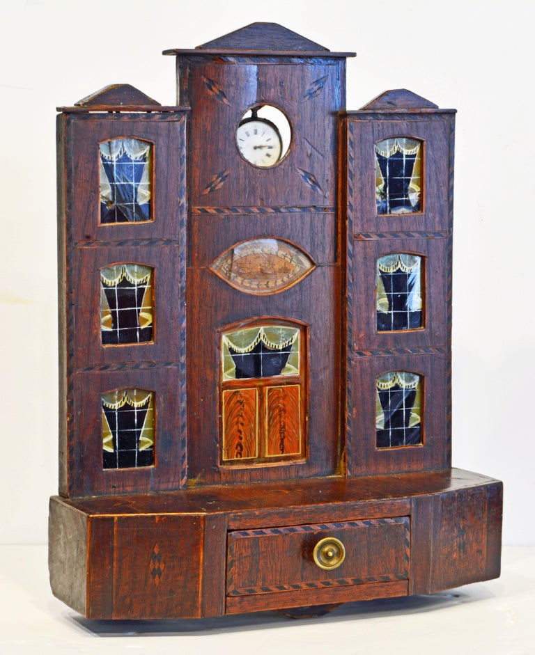 This early American inlaid pocket watch hutch or stand is made in the form of a three story house on a base with one drawer. The door and windows are made of glass painted on the backside. The piece is beautifully inlaid in a nautical theme and