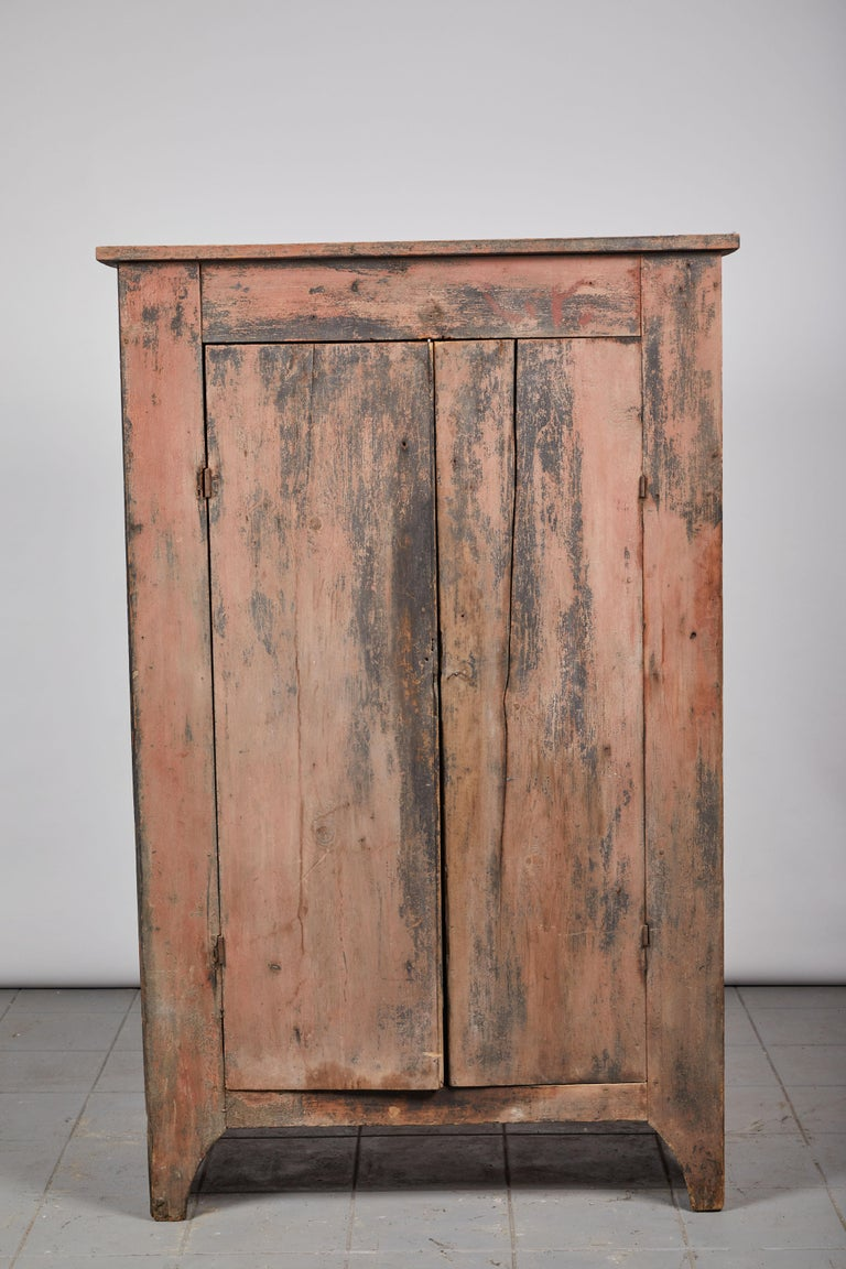 Early American rustic two-door cabinet painted with hues of pink and black. Interior consists of three shelves.