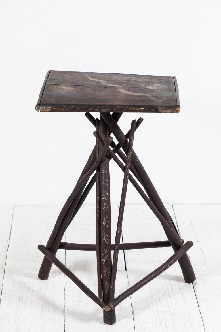 Rustic early American Adirondack style tall side table with stained twig legs and hand painted stenciled top.