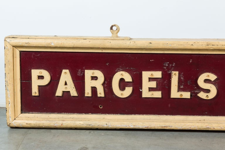 Northeastern United States cloakroom sign from rural train station, circa 1900s thick cut wood and heavy iron strapping. Lettering are individually cut out wood pieces. Double sided. One side appears to have been exposed to the elements. One side in
