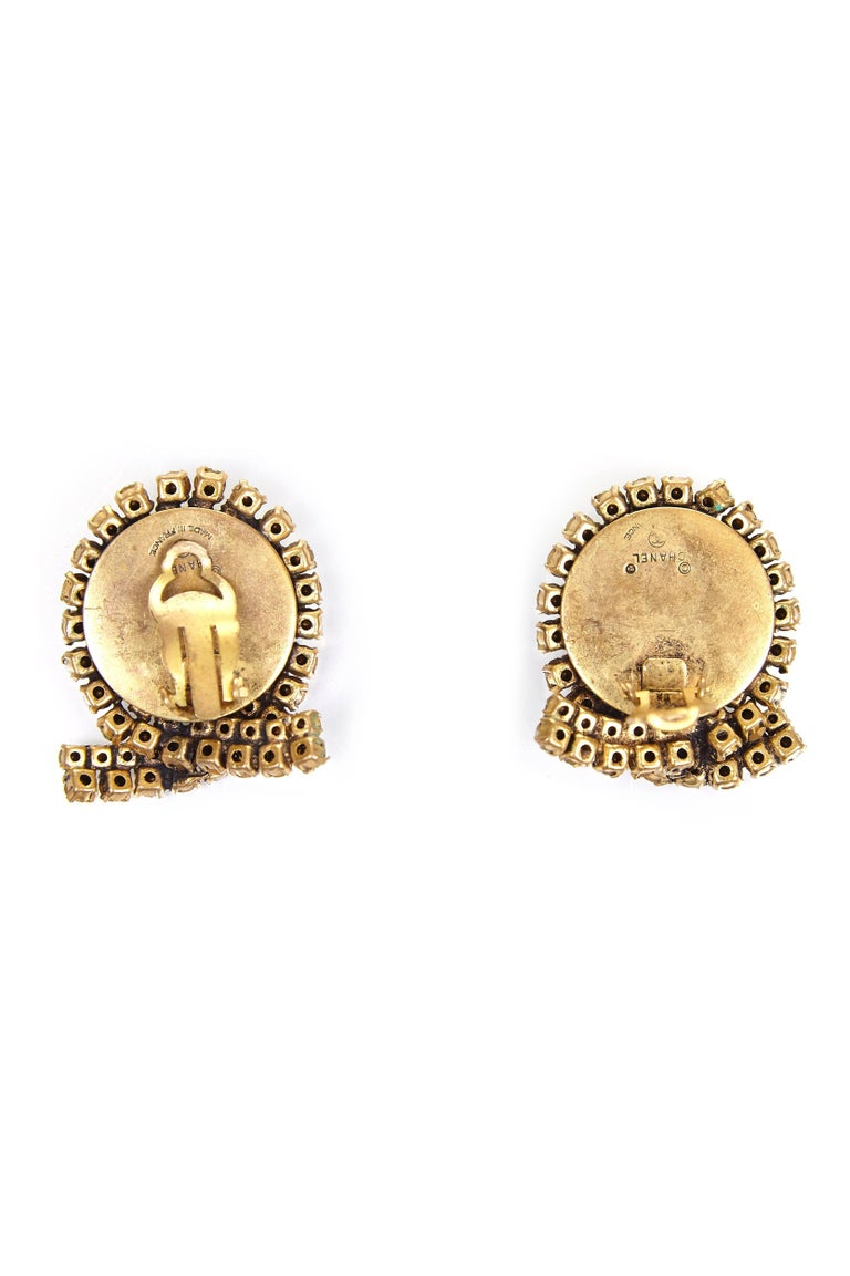 These very early 1980s Chanel earrings are beautifully made and an impressive size.  All the rhinestones are individually prong set encircling a large green cabochon glass stone.  Unusually for gripoix poured glass, this has an uneven surface but is
