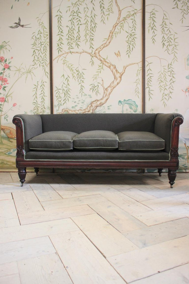 A fine quality, early 19th century period English sofa in mahogany having been reupholstered by us in a wool with contrast piping.  This elegant English period sofa will work well in most settings.  England  Measurements: 54 cm High (floor to