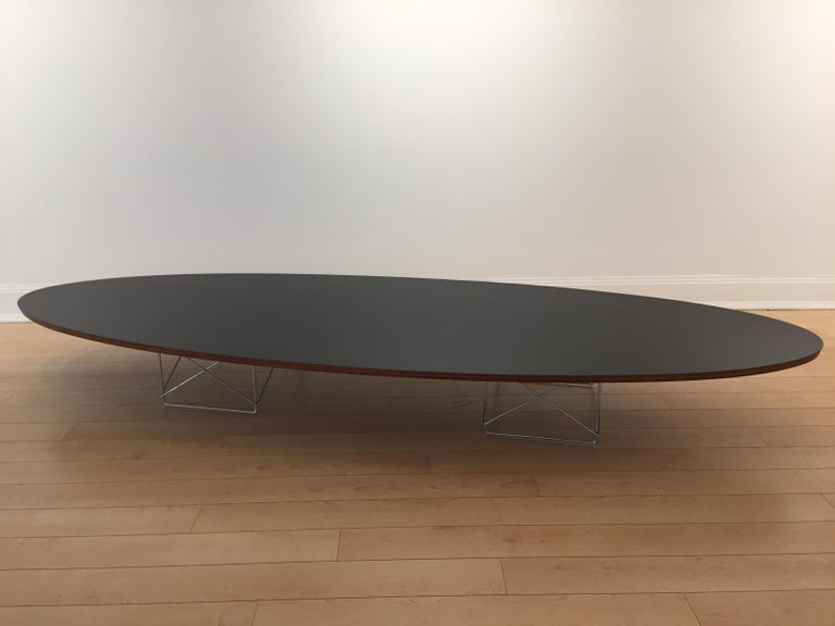 Early ETR (elliptical Table rod base) surfboard table by Charles and Ray Eames with black formica top, Aluminum basket base and edge in layered wood, original condition with early metal round tag. Charles Eames for Herman Miller.