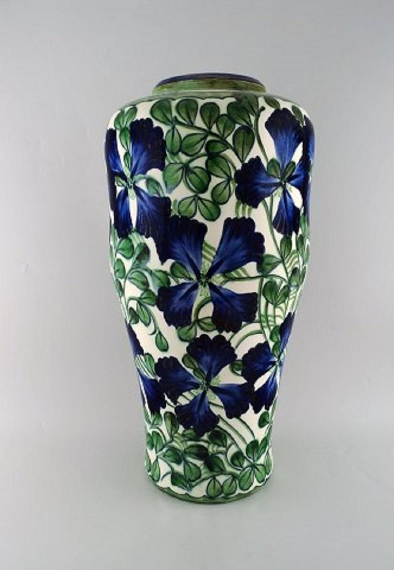 Early colossal Alumina vase in faience. Blue flowers and green leaves on a cream-colored background, early 20th century. Measures: 55 x 29 cm. Stamped. In very good condition.