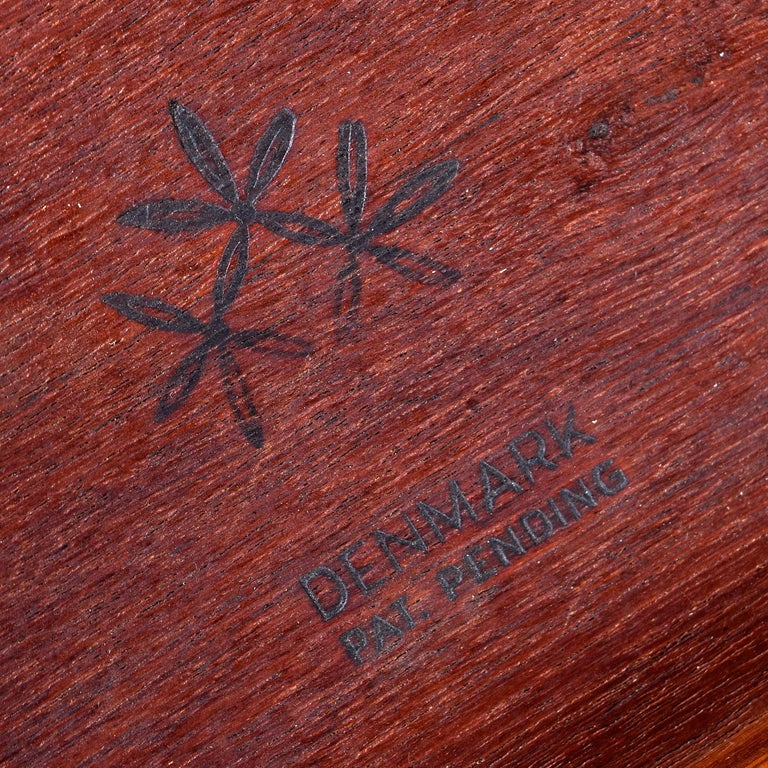 Take a look at the stamp under this table. We've never seen it before and had no luck deciphering the maker or designer. We suspect it may be very early Hans Wegner, but we're not certain. Our instincts however tell this is a significant piece of