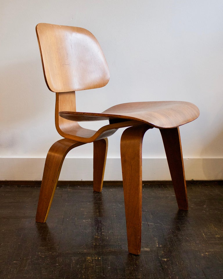 Early example of the DCW by Charles and Ray Eames. Manufactured by Evans Production Company in California, USA, 1940s.  Lovely example of Eames' plywood dining chair with five-two-five screw configuration, original shock-mounts and three-part