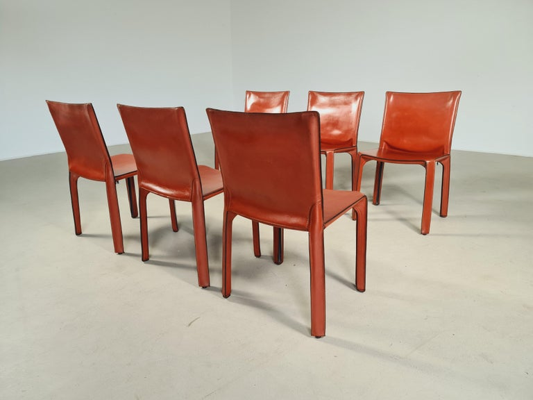 Set of 6 CAB-412 dining room chairs in Russian Red (also known as Bulgarian Red) saddle leather. Designed by Mario Bellini and manufactured by Cassina in the 1970s in Italy. These chairs are the early edition. The leather cover is stretched over a