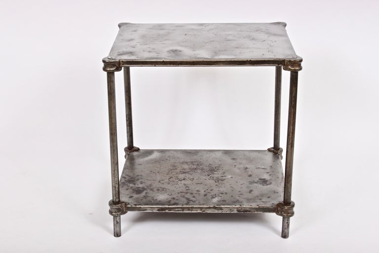 Industrial iron two shelf factory table, single nightstand, end table, tv stand, circa 1900. Featuring a rectangular form with two levels of Iron sheet metal, Iron rods, Iron pipe, corner castings and pinned corner detail. Bottom Shelf 4H from