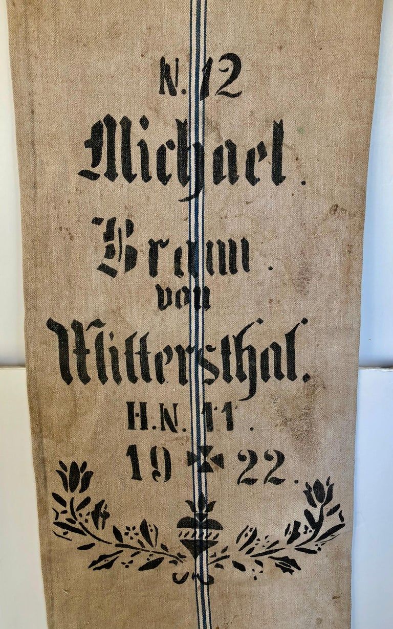 Early German handwoven grain sack with original calligraphy and graphics. It was made from linen and hemp by the farmer's wife and used to store grains in the barn. The farmer's name, town inventory # were stamped with black tar, it is very rare to