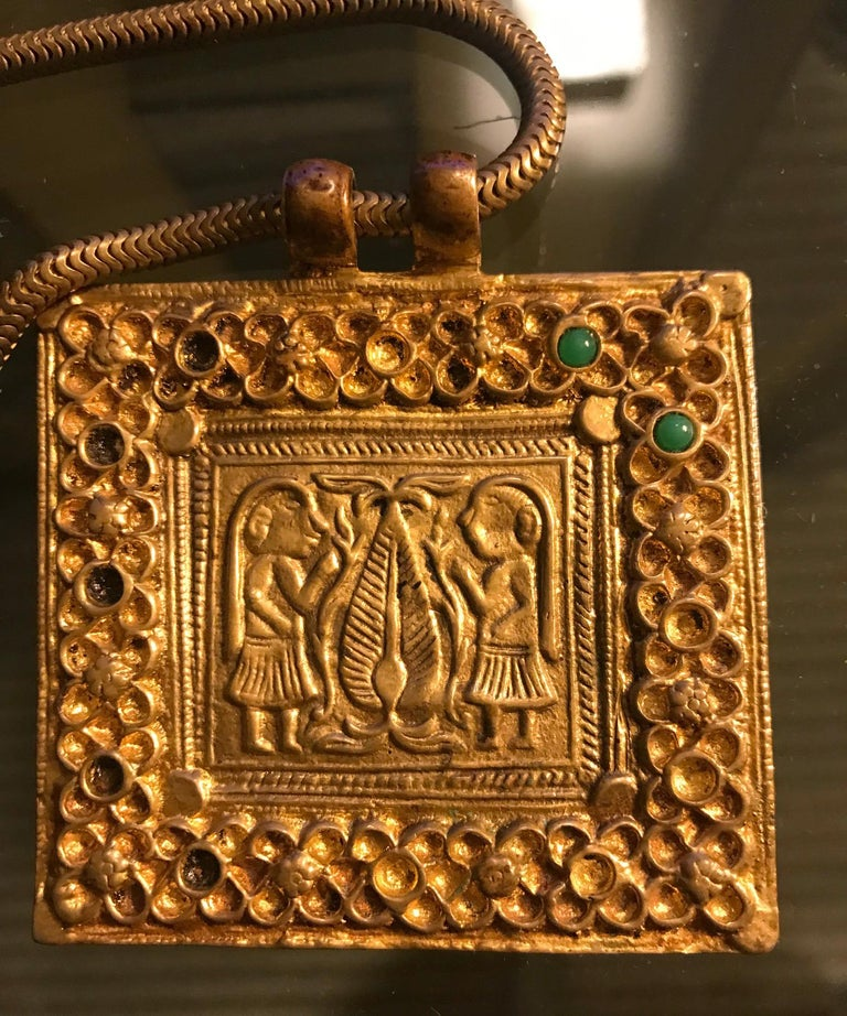A gilt bronze necklace with chain and a square plaque on the subject of