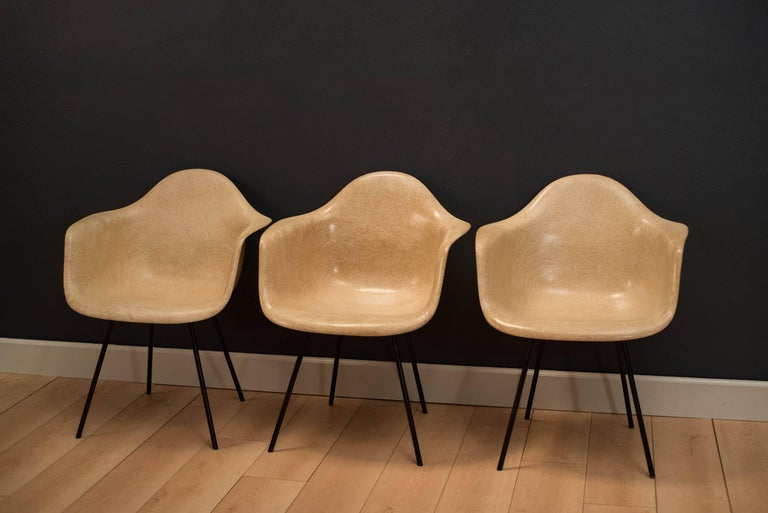 Iconic design by Ray and Charles Eames, these second generation parchment colored shell chairs have large shock mounts and original black X bases. These earlier production pieces were manufactured by Zenith Plastics.