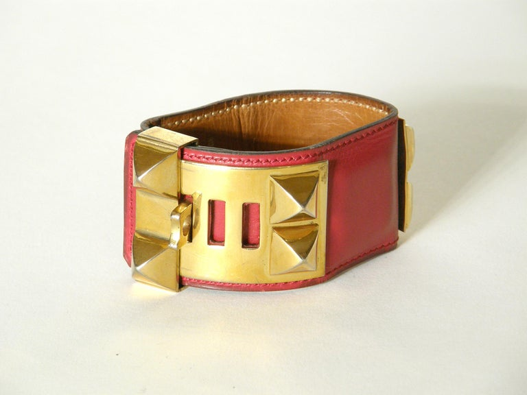This iconic Hermès Collier de Chien cuff bracelet is made of lipstick red leather with gold plated hardware. This classic design was adapted from a custom designed dog collar made for a private client of Hermès in 1923. Due to the popularity of the