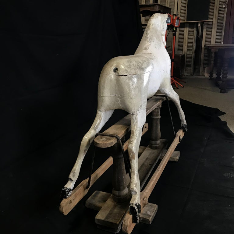 Beautiful early British carousel horse with a stunning whitewashed patina and glass eyes resting on a wooden pedestal support. A sculptural piece of art and eye catching Folk Art focal point. Weathered, small losses and old repairs add to its