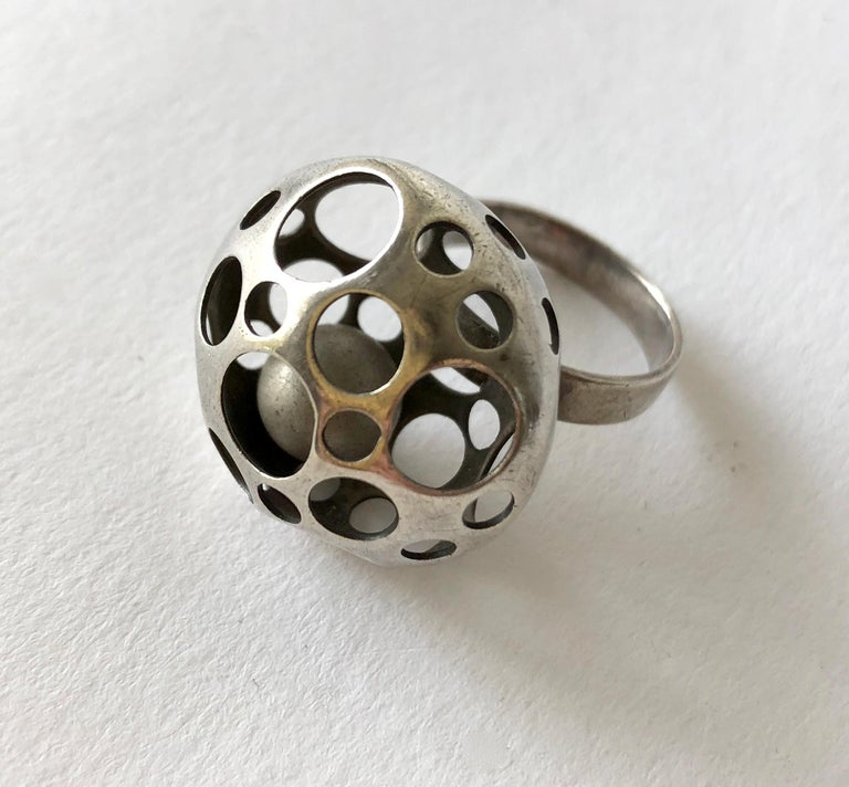 Perforated sterling silver ring containing a kinetic ball within created by Liisa Vitali of Finland.  Ring is a finger size 6 3/4 and is signed on the shank with Finnish hallmarks, M7 (1965).  In very good vintage condition and retains original