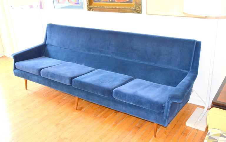 Striking angular sofa by Milo Baughman for Thayer Coggin. Wing like angular forms with tapered conical dowel legs, previously reupholstered in a royal blue velvet fabric. Long and sleek proportions with generous seating area yet extremely