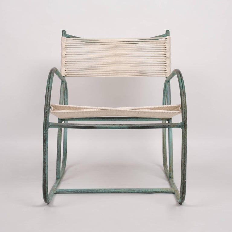 A 1940s Walter Lamb lounge chair predating his partnership with Brown Jordan, this piece has an angled backrest bisecting two rounded runner arms. The patinated frame in tubular bronze is strung with cotton-nylon sail cord, woven to form a seat and