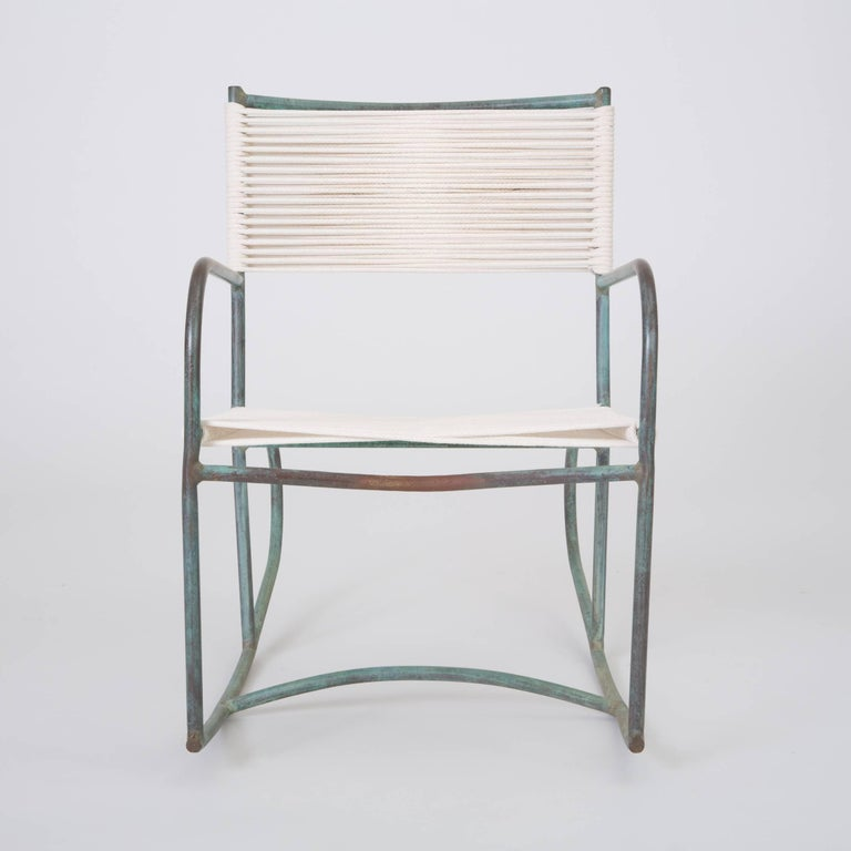 A late 1940s or early 1950s Walter Lamb rocking chair predating or from the early days of his partnership with Brown Jordan. The chair has a frame in tubular bronze with the verdigris patina that distinguishes his designs. Two runners with bowed