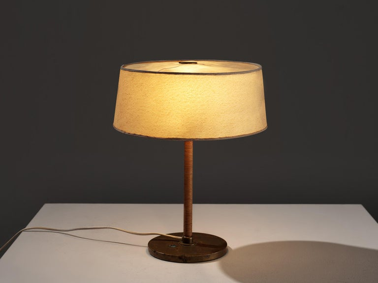 Paavo Tynell for Oy Taito Ab, table lamp, brass, cane, iron, Finland, 1930s  Early Paavo Tynell table lamp designed for Taito. This esquisite table lamp already holds all the characteristics of a true Tynell design. The slim stem covered in cane,