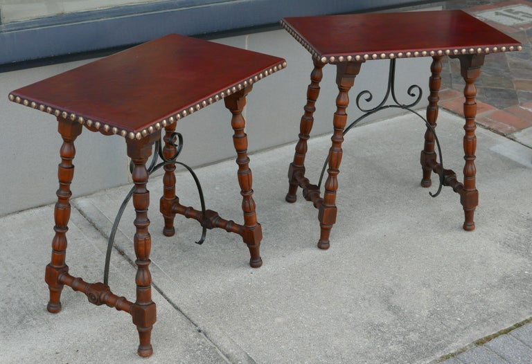 Wonderful leather top tables with large nailhead trim and Spanish colonial base in solid oiled walnut with forged iron brackets for the trestle-like base. Rare to see one of these tables, which would fit in wonderfully in a Southwest or southern