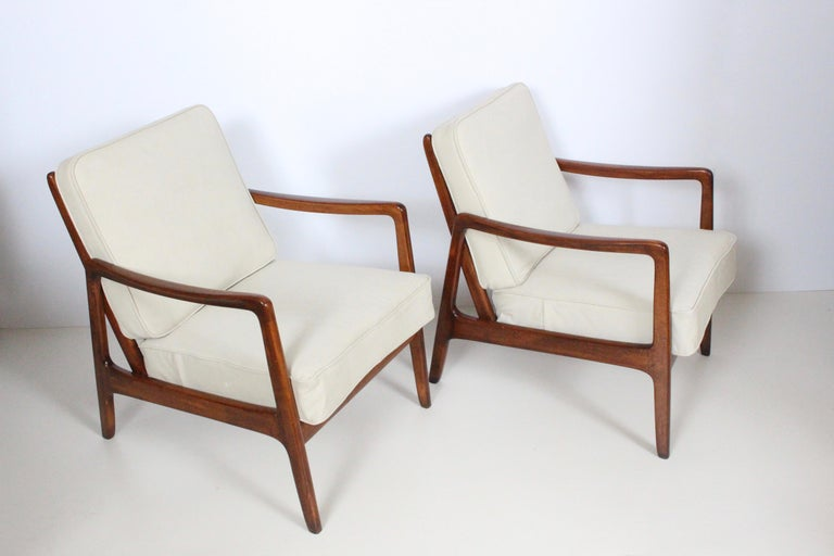 Danish modern pair of solid Cuban mahogany lounge armchairs by Ole Wanscher designed for France and Daverkosen distributed by John Stuart. Featuring solid and sturdy mahogany angled ladder back style framework for ultimate comfort, with newly