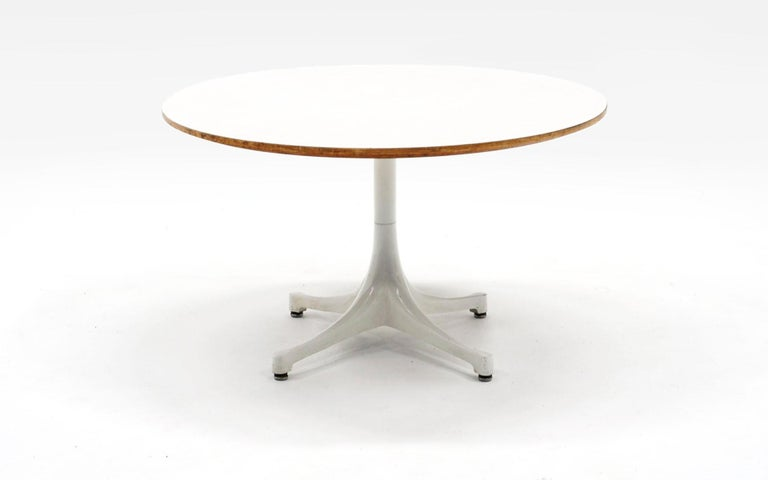 Round white pedestal coffee / side table designed by Irving Harper for the George Nelson Office and made by Herman Miller between 1954-1957. Signed with the early Herman Miller George Nelson round white metal medallion. White laminate top and