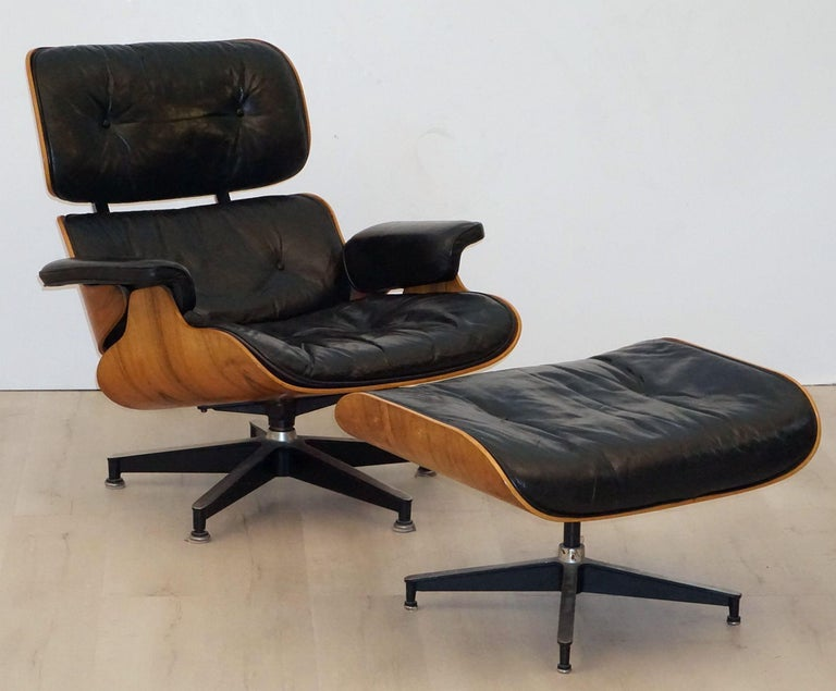 A fine early production Eames lounge chair with ottoman by Herman Miller, circa 1965, with original tufted black leather upholstered cushions.  The Brazilian rosewood (Rio Palissander) has a beautiful wood grain and is in excellent vintage