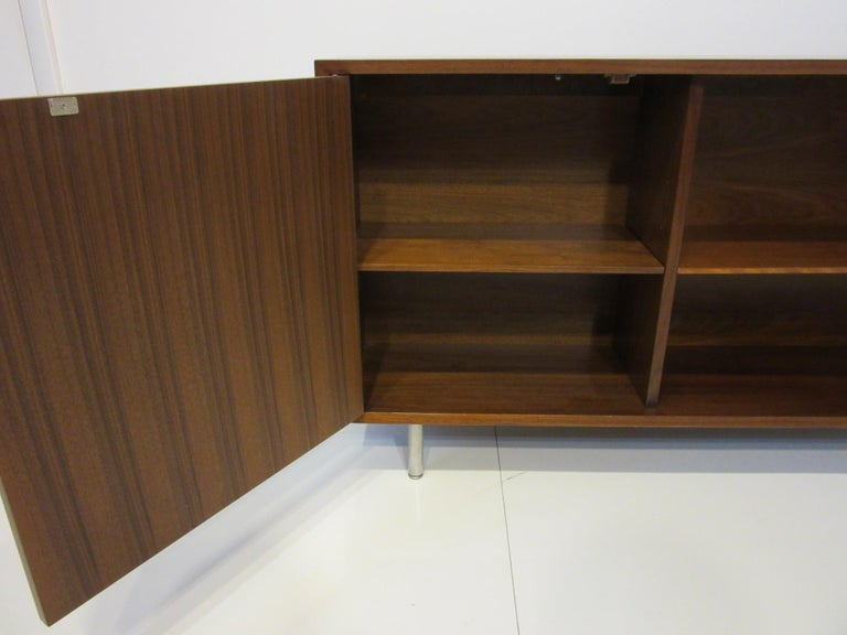 A rare sized console/ credenza / bookcase cabinet in beautifully grained walnut with left no pull door exposing an adjustable shelve and another one to the right side sitting on brushed stainless steel legs. This early cabinet retains the foil