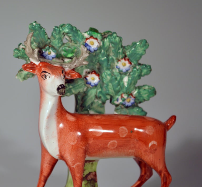 Early Staffordshire pearlware pair of deer Bocage figures,  circa 1825.  The charming pair of bocage figures depict a spotted red stag and deer facing each other. They Stand with bocage behind and on a hollow mound base naturalistically coloured