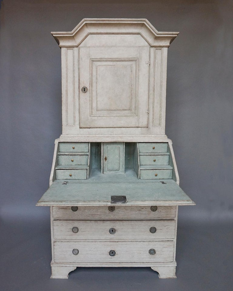 Slant-front secretary in two parts, Sweden, circa 1790. The upper section has an arched cornice and single paneled door, with two interior shelves, the top one shaped and notched for spoons. The lower section has three full width drawers and a