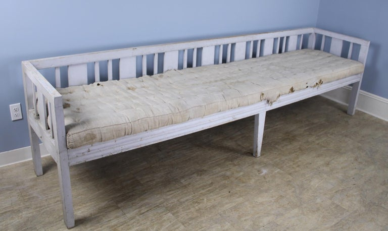 We don't see this kind of piece often. Quite early with exceptional proportions - almost 9.5 feet long with original paint and horse hair stuffed cushion, ready for reupholstery. This piece is very sturdy and resplendent with rustic charm. Has been
