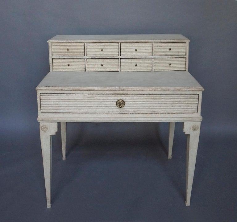 Period Swedish writing desk, circa 1820, with early hutch fitted with 8 small drawers. Full-width drawer below the writing surface, and shaped legs with applied roundels in the slightly later base.