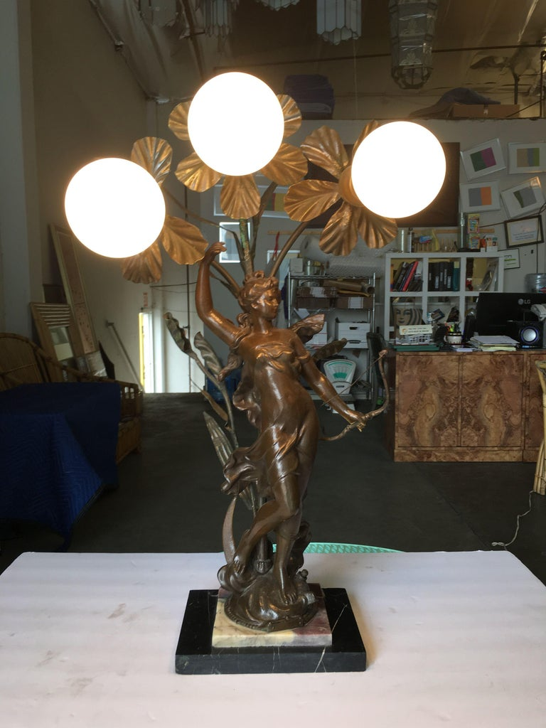 Early three bulb Art Nouveau figural table lamp featuring a beautiful figural casted bronze female fixed to a two-piece, two-tone marble base topped with an organic freeform floral featuring 3 standard light sockets.