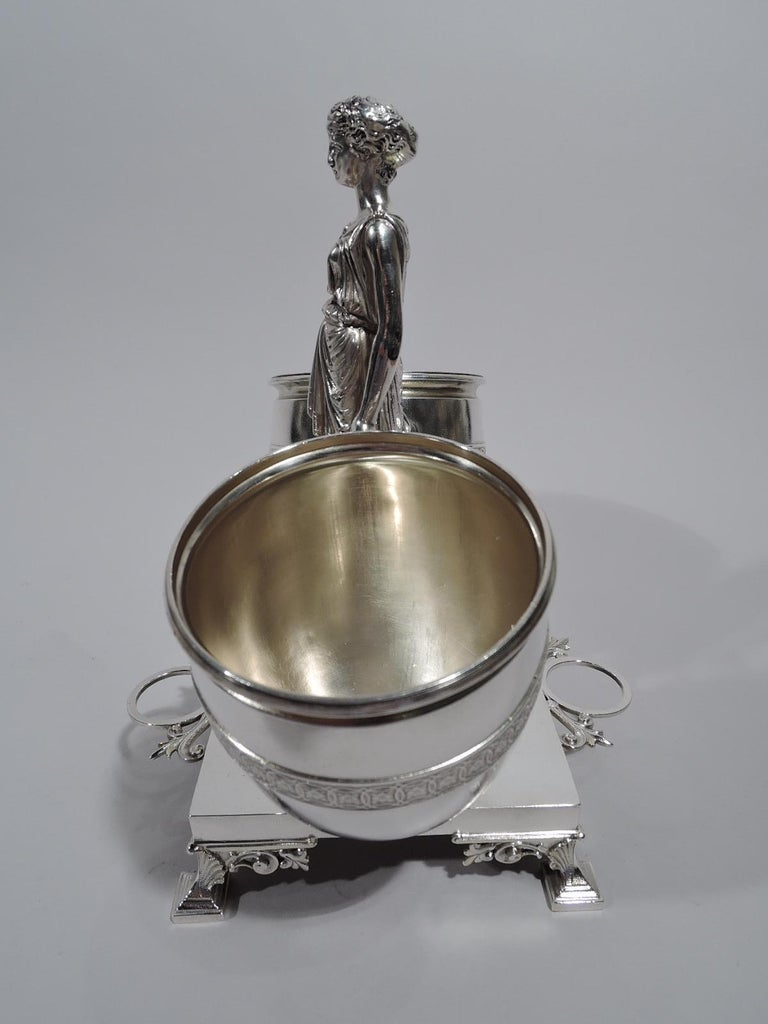 Classical sterling silver cigar holder. Made by JC Moore & Son for Tiffany & Co. in New York. The cast-figure of a draped and barefooted maiden standing on pedestal and gripping two oversized amphoras with gilt-washed interior and rosette-inset