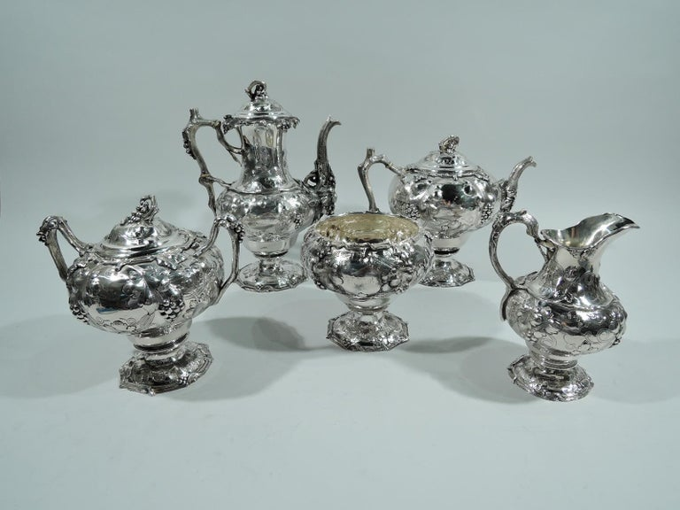 Early sterling silver coffee and tea set. Made by John C. Moore for Tiffany & Co. in New York in 1850s. This set comprises 5 pieces: coffeepot, teapot, creamer, sugar, and waste bowl. Chased and engraved grape bunches and leaves as well as vine