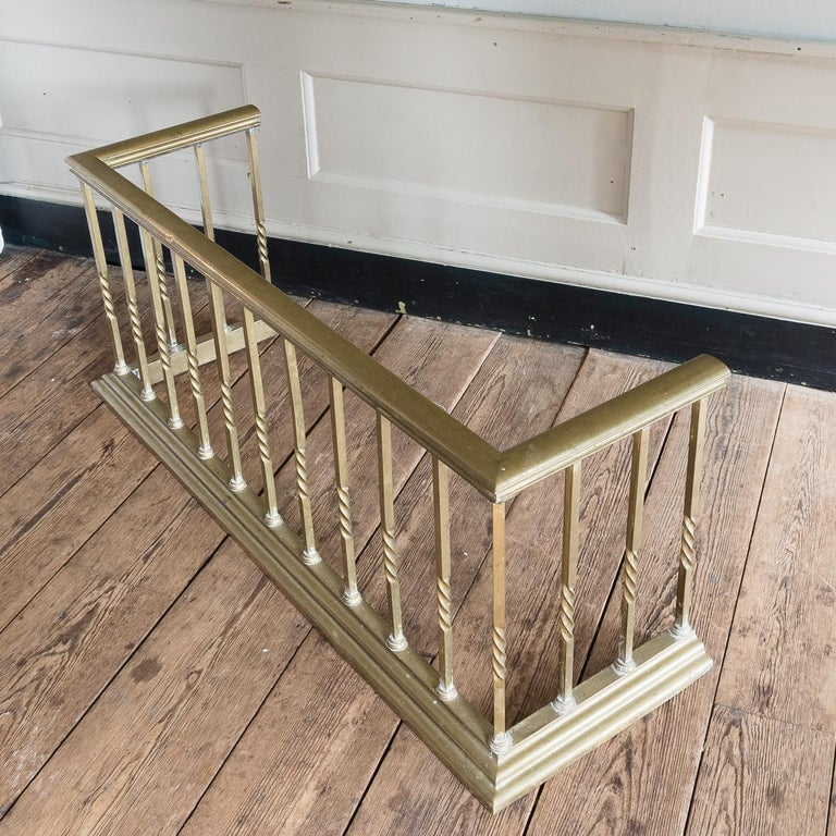 Early 20th century English brass club fender, the brass seat rail on square section supports, each wrythen to the centre.