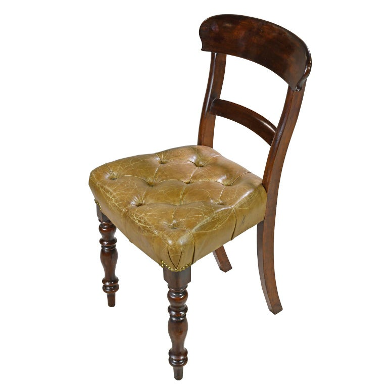An early Victorian side chair in mahogany with curved top rail, and raised on turned front legs and saber back legs. Seat is upholstered in a tufted, beige/camel-colored leather with brass nailheads, England, circa 1840. Note: A pair of side chairs