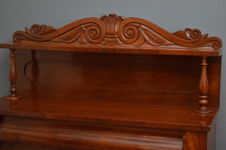 K00 early Victorian chiffonier in mahogany, having carved upstand with a shelf on turned supports, figured mahogany top and a shaped frieze drawer above a pair of panelled cupboard doors fitted with working lock and a key, all standing on plinth