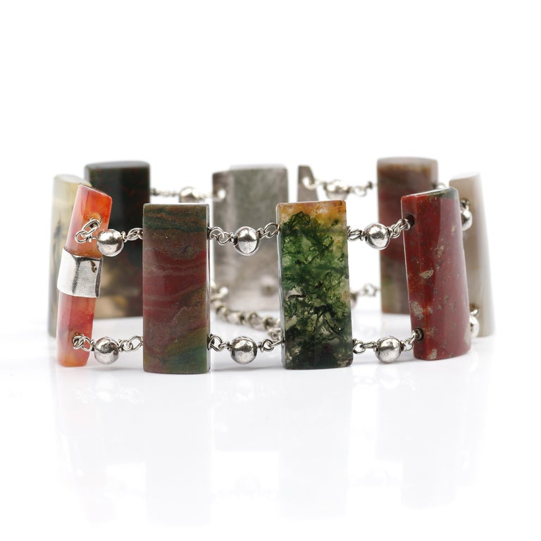 A stunning and uncommon early Victorian (circa 1850s) bracelet was hand-crafted in silver and features eight hand-carved and polished agate gemstones.  Among the different varieties of agate in the bracelet are Scottish Montrose agate, moss agate,